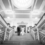 the bride & groom decend main stair case at Islington Town Hall